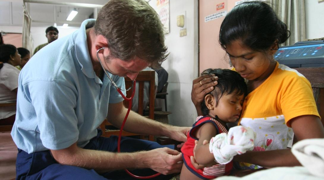 Projects Abroad male intern is seen performing a check up on a baby as part of his midwifery internship in Sri Lanka.